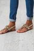 stock photo of habilis  - Woman legs in blue jeans and summer shoes - JPG