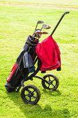 foto of golf bag  - a wheeled golf bag full of golf clubs of a vibrant golf course - JPG