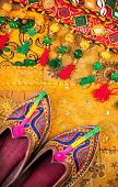 image of flea  - Colorful ethnic shoes and gipsy belt on yellow Rajasthan cushion cover on flea market in India - JPG