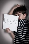foto of scared  - Scared and abused young boy holding the paper with handwritten help sign - JPG