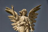 foto of spread wings  - A stone angel with wings spread against the sky - JPG