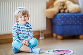 picture of indoor games  - Funny little boy of three years playing with puzzle game at home - JPG