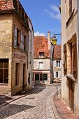 foto of cobblestone  - Cobblestone lane in a town in Burgundy France with boulangerie - JPG