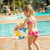 foto of pool ball  - little cute girl playing near the pool with a ball - JPG