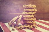 stock photo of chocolate-chip  - Stack of chocolate chip cookies on red and white stripe napkin against a dark wood background with applied vintage style filters and added light stream - JPG