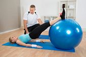 picture of pilates  - Male Instructor Looking At Woman Exerting With Pilate Ball - JPG