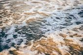 stock photo of cape-cod  - Bubbly sea foam swirling over golden sands at sunset on a beach at Cape Cod - JPG