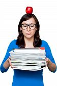 Nerdy Young Female With Books And Apple Placed On Her Head Isolated