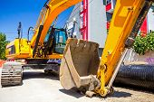 foto of backhoe  - Excavator loader with backhoe is standing over blue sky in city street - JPG