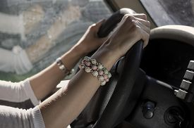 stock photo of steers  - Side shot of female hands wearing bracelet on a steering wheel reflection in the blurred background - JPG