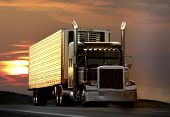 stock photo of trucks  - big truck driving on a highway with sunset in background - JPG