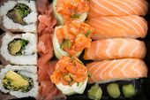 Tray of assorted sushi against white background poster