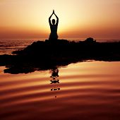 stock photo of yoga silhouette  - Woman doing yoga at sunset on the seashore - JPG