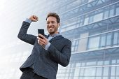Success winner business man winning on cellphone app. Cheering businessman looking at smartphone onl poster