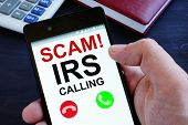 Hand Is Holding Phone With Irs Scam Calls. poster