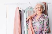 Confident Senior Lady At Work. Fashion Boutique Business. Successful Elderly Lady Posing By Rack Of  poster