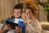 technology, internet banking and people concept - happy couple using tablet computer and credit card poster
