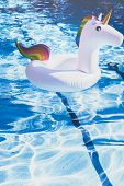 Inflatable Colorful White Unicorn At The Swimming Pool. Vacation Time In The Swim Pool With Plastic  poster