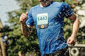Male Runner Running Marathon In City In Foreground Splashing Water poster
