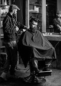 Barber Preparing Hair Clipper For Bearded Man, Barbershop Background. Barber With Clipper And Brutal poster
