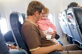 Young Tired Father And His Crying Baby Daughter During Flight On Airplane Going On Vacations. Dad Ho poster