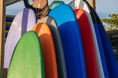 Stack Of Different Color Surf Boards In A Stack By Ocean.bali.indonesia. Surf Boards On Sandy Beach  poster