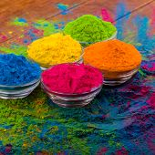 Bright colourful powdered pigments in glass bottles for Indian holi festival on dark slate backgroun poster
