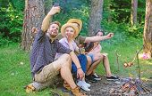 Friends Near Bonfire Enjoy Vacation And Roasted Food. Tourists Sit Log Near Bonfire Taking Selfie Ph poster