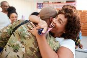 Millennial black soldier returning home to his family, embracing his mother, close up poster