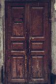 Peeling Brown Wooden Door. Dilapidated Wooden Grunge Door With Cracked Maroon Paint. Threadbare Dark poster