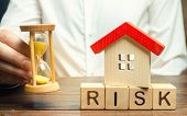 Wooden Blocks With The Word Risk, The House And The Clock. The Concept Of Non-payment Of Interest Ra poster