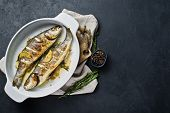 Baked Sea Bass In A Baking Dish. Black Background, Top View, Space For Text poster