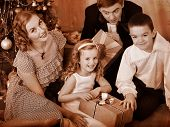Happy family with children  receiving gifts under Christmas tree. Black and white retro.
