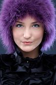 Closeup portrait of happy beauty smiling in funny purple wig.