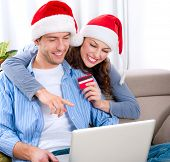 Christmas Online Shopping. Happy Smiling Couple Using Credit Card to Internet Shop. Young couple wit