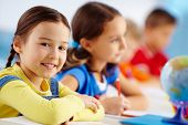picture of diligent  - Portrait of lovely schoolgirl at workplace looking at camera with her classmates behind - JPG