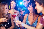Portrait of joyful friends toasting at birthday party with focus on two laughing girls