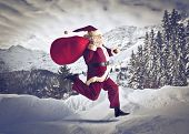 Santa Claus running on the snow with his sack of presents