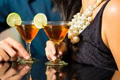 Man and woman flirting intimately at bar drinking cocktails