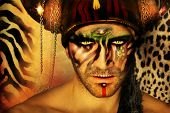 picture of cannibal  - Fashion stylized concept portrait of a young man with tribal face painting and animal elements in front of a animal print background - JPG