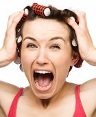Young woman is screaming in terror holding her head with hands while wearing hair-rollers, isolated