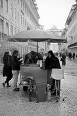 RUA AUGUSTA, LISBON, PORTUGAL - 02 NOVEMBER 2012 - A street roasted chestnut seller plies his trade