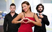 stock photo of threesome  - Woman Standing In Front Of Men Making A Heart Shape Sign - JPG