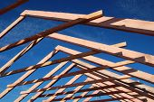 Wood Roof Trusses viewed from inside of new home looking out to a blue sky above .Ukraine