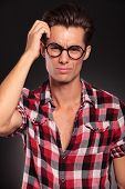 confused casual man with glasses sctratching his head