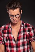 casual fashion man wearing glasses looking down on dark background