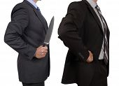 Stabbed in the back concept conflict in the office one businessman holding a knife and stabbing anot