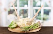 Plate with coleslaw, asparagus and chicory on wooden table on window background