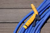 Blue water hose with a yellow nosel
