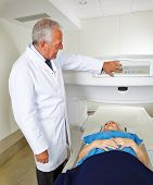 Doctor and senior patient at MRI machine in radiology in a hospital
